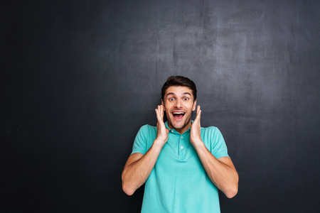 mouth opened: Cheerful surprised young man with mouth opened standing over chalkboard background Stock Photo