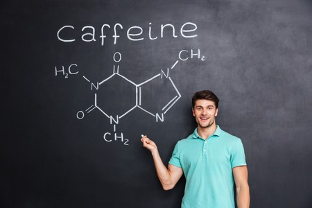 hormone  male: Smiling confident young student standing and showing chemical structure of caffeine molecule drawn on blackboard background
