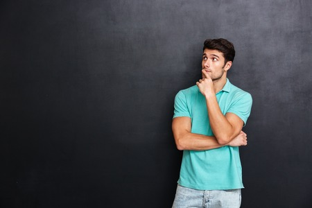 handsom: Pensive handsome young man standing with hands folded and thinking over blackboard background Stock Photo