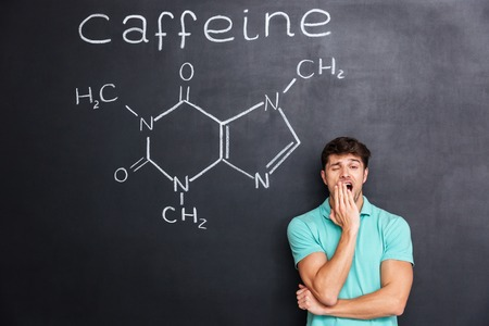 chemical structure: Exhausted fatigued young man yawning over chalkboard background with drawn chemical structure of caffeine molecule Stock Photo