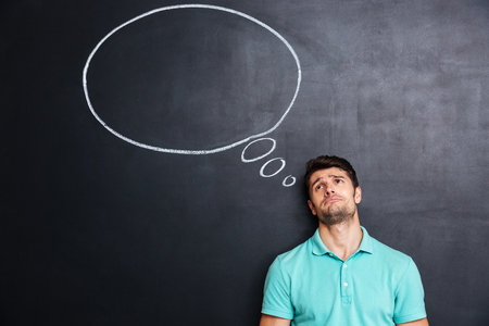 despaired: Unhappy despaired young man over blackboard background with blank speech bubble