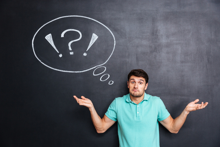 perplexed: Confused perplexed young man shrugging shoulders over chalkboard background with blank speech bubble Stock Photo