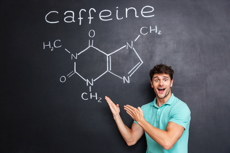 caffeine molecule: Happy excited young scientist standing and showing chemical structure of caffeine molecule drawn on chalkboard background