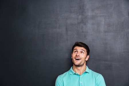 mouth opened: Wondered happy young man with mouth opened looking up over blackboard background Stock Photo