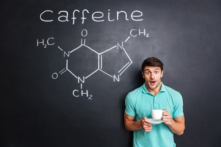 hormone  male: Surprised young student drinking coffee over drawn chemical structure of caffeine molecule on blackboard