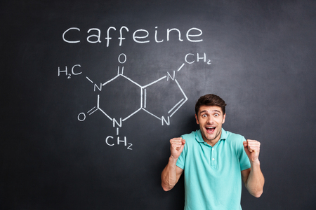 hormone  male: Happy excited young man celebrating success over drawn caffeine molecule chemical structure on chalkboard background