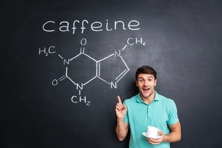 hormone  male: Smiling young man drinking coffee and pointing on drawn caffeine molecule chemical structure on chalkboard background
