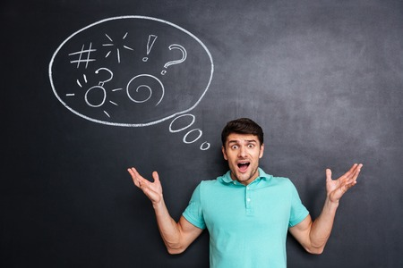 Angry astonished young man standing and shouting over blackboard background with speech bubble