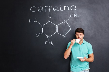 caffeine molecule: Handsome young man drinking coffee over blackboard background with drawn chemical structure of caffeine molecule
