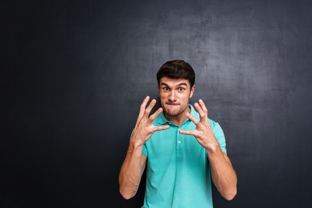 irritated: Angry irritated young man in blue t-shirt over chalkboard background