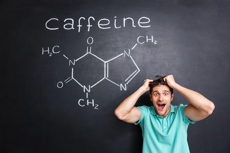 Crazy cheerful young professor of chemistry standing and shouting over chalkboard background