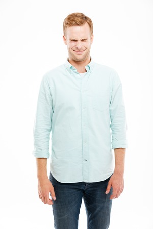 squint: Smiling cute young man standing and squinting over white background Stock Photo