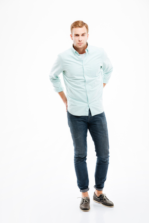 hands behind back: Full length of handsome young man in jeans and shirt standing with hands behind back over white background Stock Photo