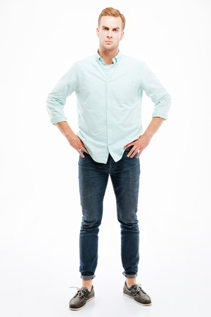 huffy: Full length of angry strict young man standing with hands on hips over white background