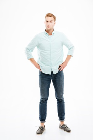 exacting: Serious suspicious young man standing with hands on hips over white background Stock Photo