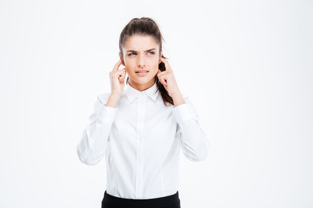 hands covering ears: Young depressed businesswoman covering her ears with hands isolated on a white background