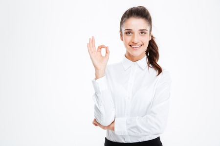 copyspace: Happy young businesswoman showing ok sign isolated on a white background