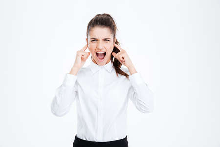 hands over ears: Young businesswoman covering her ears with hands and shouting over white background