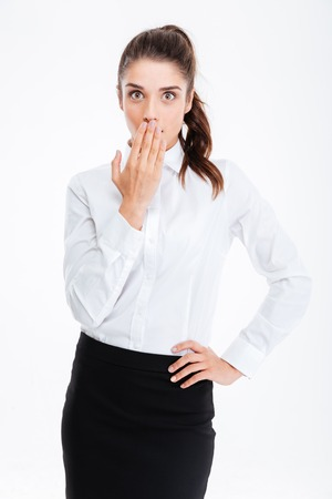 prankster: Young beautiful businesswoman covering her mouth with palm isolated on a white background Stock Photo