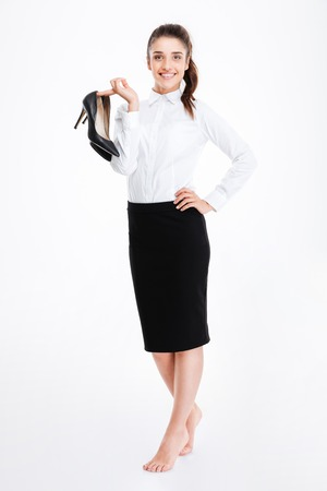 lovely businesswoman: Smiling lovely young businesswoman standing barefoot and holding high heels shoes over white background Stock Photo