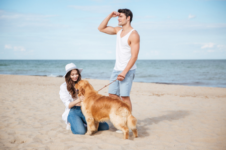 Young beautiful couple in love playing with their dog on the beach