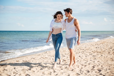 casua: Beautiful young couple talking and walking on the beach together
