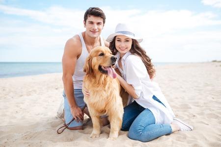 Hermosa joven pareja con su perro en la playa en verano