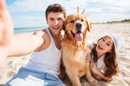 Joven pareja feliz con el perro tomando una autofoto en la playa Foto de archivo