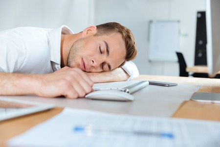 fatigued: Exhausted fatigued young businessman sleeping on the table in office