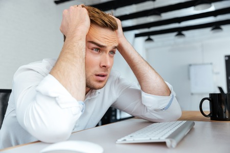 office life: Upset disappointed young businessman sitting at workplace with hands on head