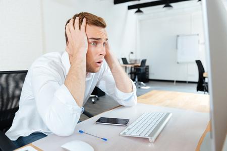 Geschokte verbaasde jonge zakenman die computer met behulp van op het werk
