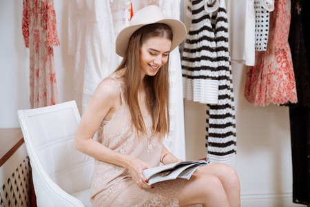 saleslady: Cheerful cute young woman in hat reading magazine in clothes shop