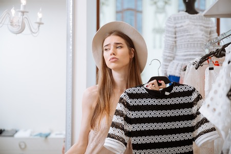 insides: Sad pretty young woman in hat doing shopping in clothing store Stock Photo