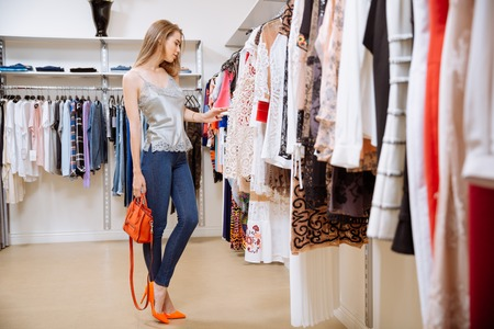 choosing clothes: Beautiful young woman standing and choosing clothes in clothing store Stock Photo