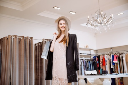 sho: Happy attractive young woman holding shopping bags and standing in clothing store Stock Photo