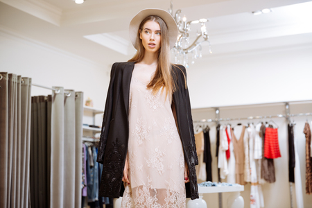 saleslady: Closeup of gorgeous young woman in dress, jacket and hat standing in clothig store
