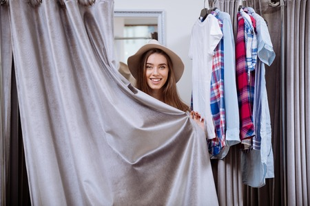 fitting room: Cheerful young woman in hat covered herself standing in fitting room