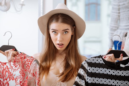 blouses: Lovely puzzled young woman in hat choosing clothes in clothing store Stock Photo