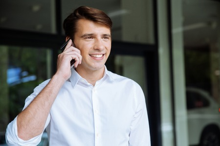 Closeup of happy young businessman talking on mobile phone near buiness center Stock Photo