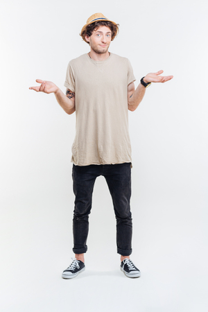 indecisive: Confused handsome young man standing and shrugging over white background