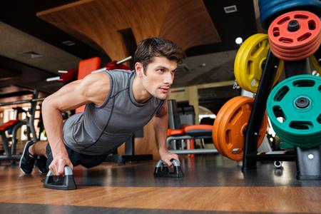 Confiamos en el hombre joven de la aptitud que se resuelve y haciendo flexiones en el gimnasio