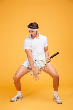 Funny playful young man tennis player with racket imitating playing guitar over yellow background Stock Photo