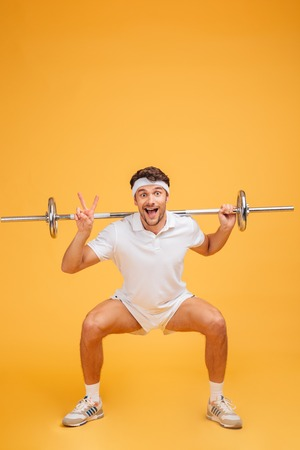 Funny cheerful young sportsman doing squats with barbell and showing peace sign over yellow background Stock Photo