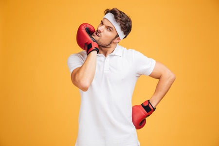 pectorals: Portrait of young man boxer in red gloves standing and warming up over yellow background Stock Photo