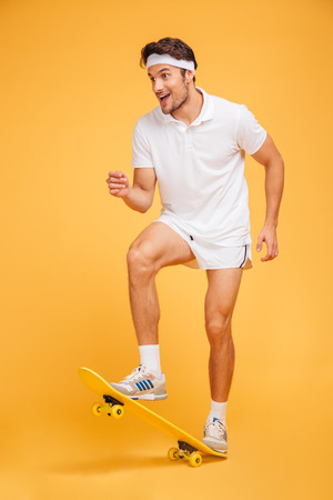 skateboarder: Happy young sports man skateboarding isolated on a orange background