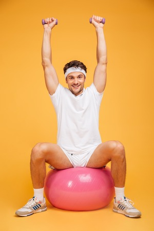 Portrait of a sports man sitting on the fitness ball and doing exercises with small dumbbells isolated on a orange background