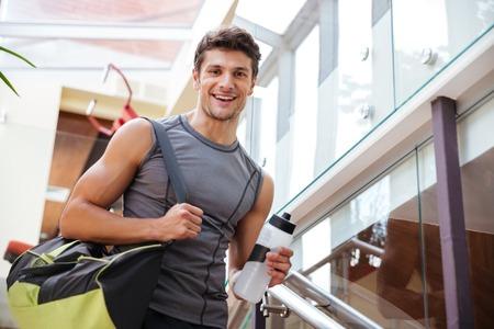 fitness joven alegre con el bolso y la botella de agua de pie en el entrenamiento en el gimnasio