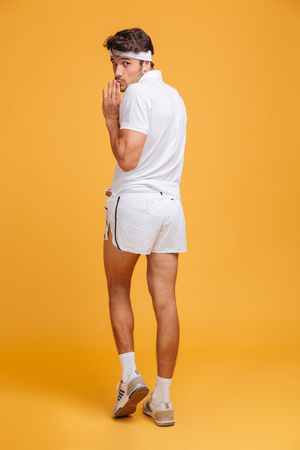 looking away from camera: Back view of funny shy young sportsman posing and grimacing over yellow background Stock Photo