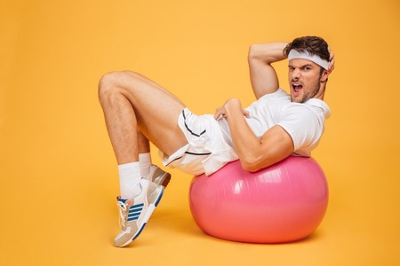 Young handsome sportsman doing abs on fitness ball isolated on the orange background