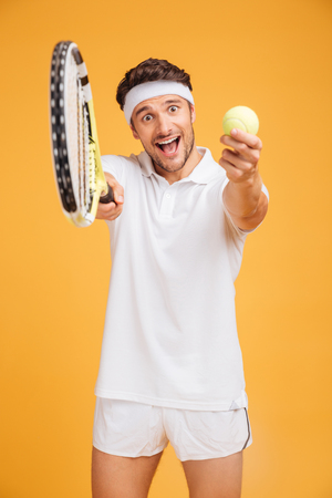 Happy young man tennis player inviting you to play over yellow background Stock Photo